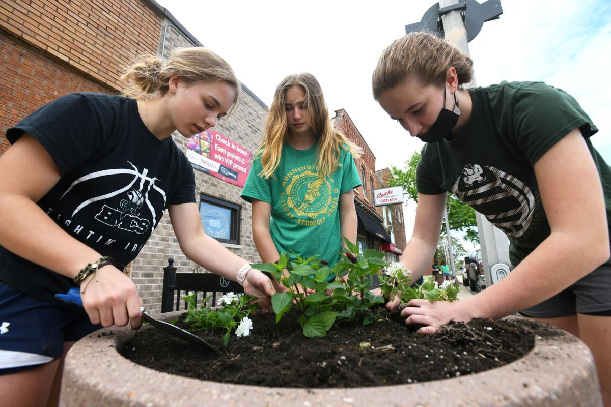 Garden club, students beautify downtown planters
