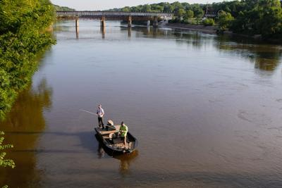 Anglers line river at sunrise for Fishing Derby