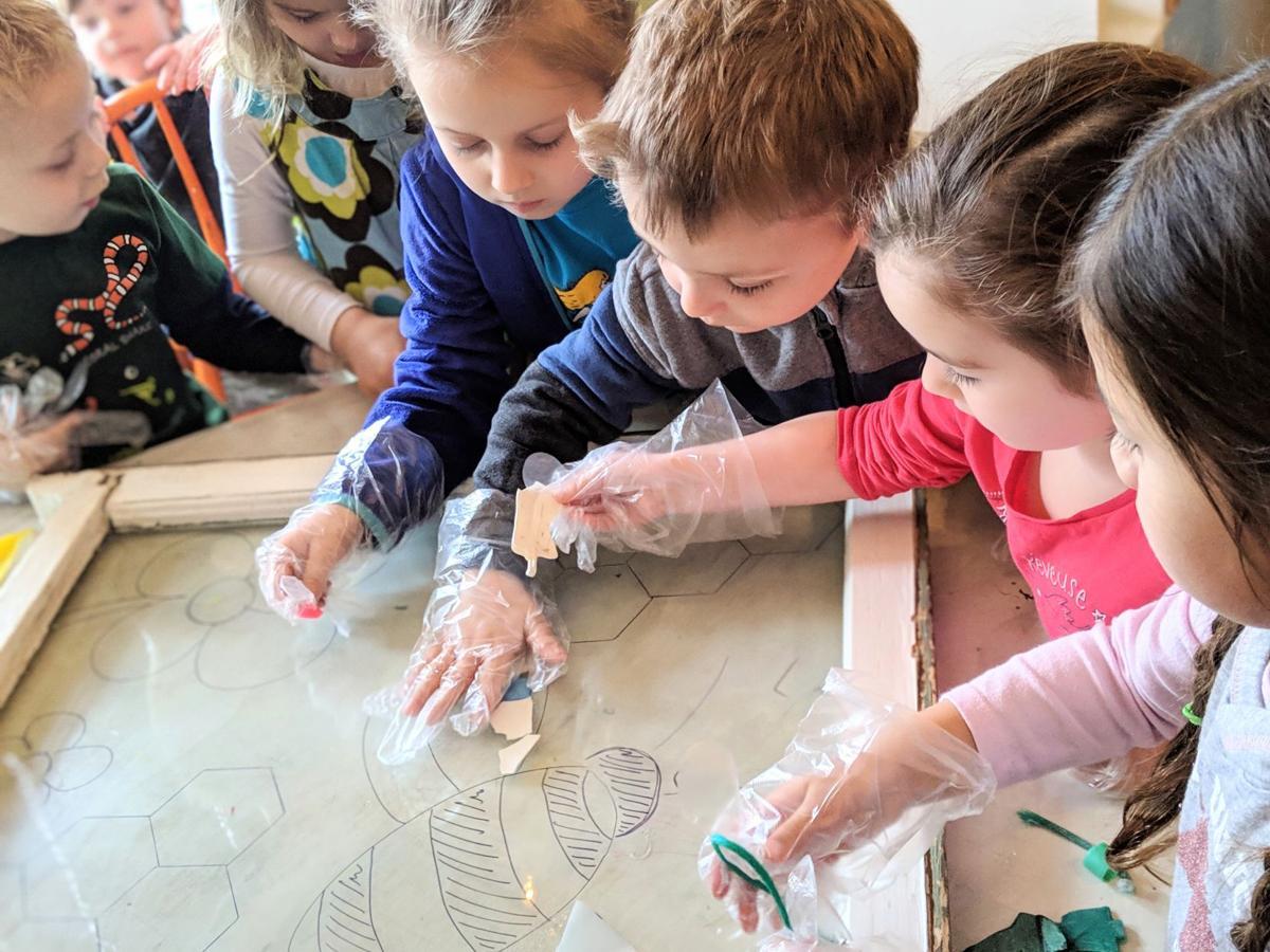 Preschoolers arrange plastic debris into a mural