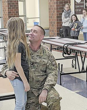 Schneider greets children after his overseas duty