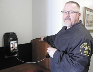 <p>LAKE COUNTY SHERIFF Tim Walburg demonstrates how video visitation will work at the Lake County Jail, enlisting a correctional officer to demonstrate what visitors will see when they use the new devices. Visitors will need to register to get a four-digit code in order to speak with a prisoner.</p>