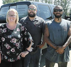 <p>JESSICA AND RANDY COX, owners of Cox Alignment &amp; Repair in Madison, pose with mechanic Adonis Rodriguez (right) outside their garage and repair shop. The Coxes opened their auto repair and maintenance business in June 2018 and have established a large body of customers.</p>