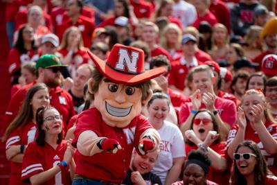 Herbie Husker points at the camera during a football game