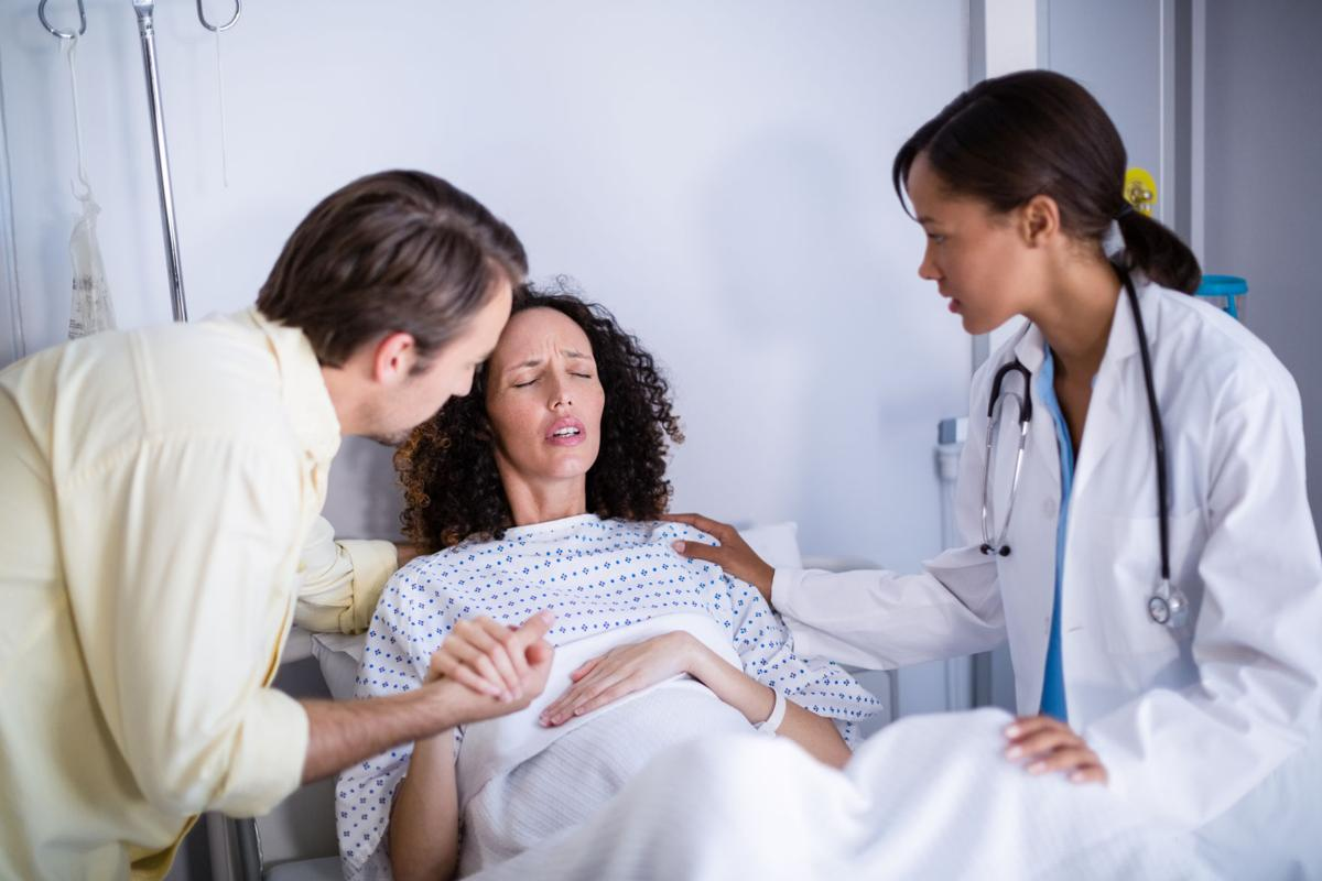 Doctor and man comforting pregnant woman in ward