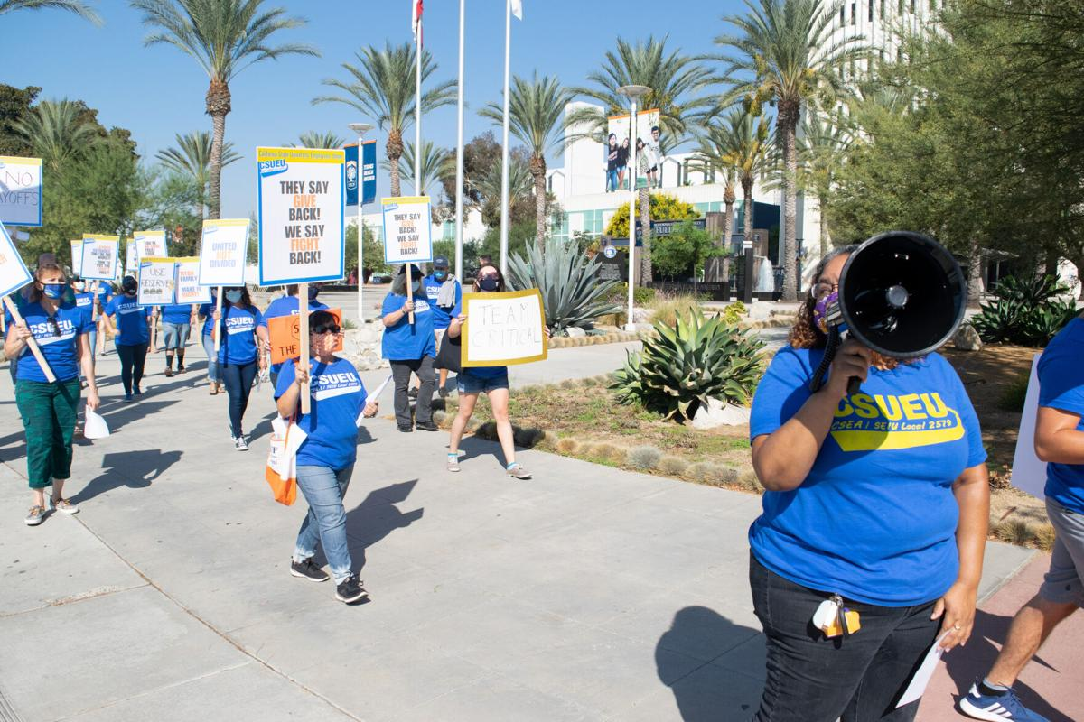 Protesters march against the layoffs of CSUF faculty on campus holding signs and wearing masks while remaining socially distanced from each other. (Natalie Solano / Daily Titan)