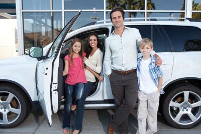 Family in front of a Sports Utility Vehicle