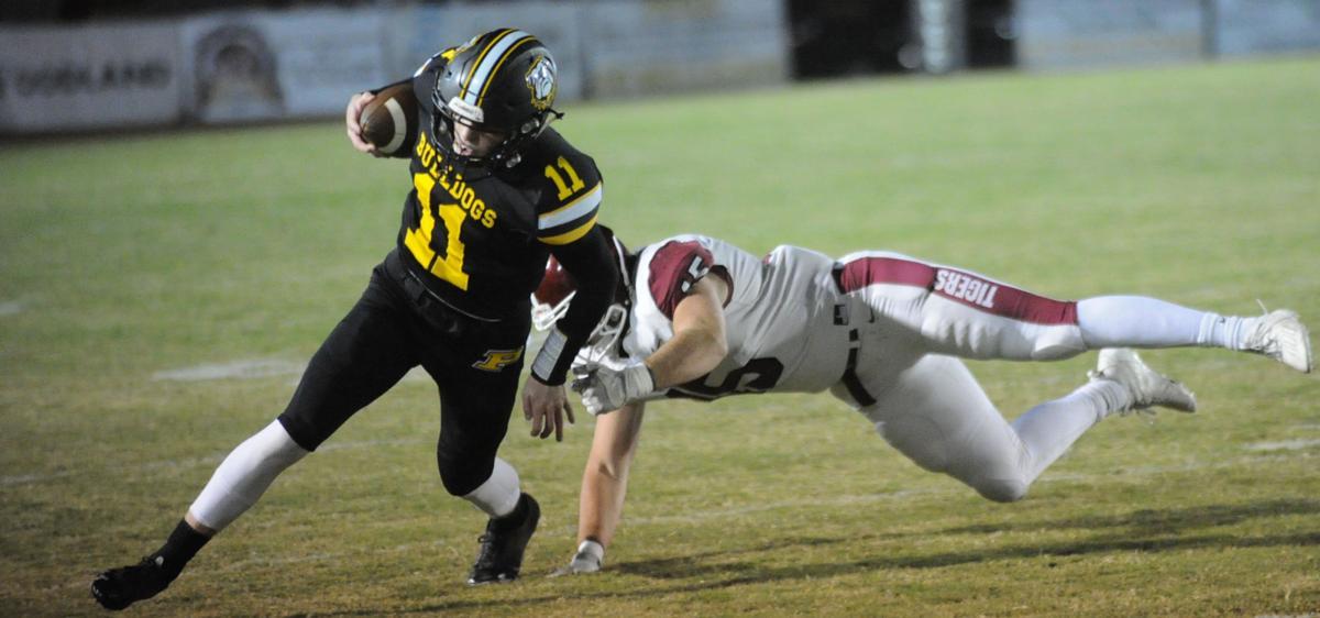 Priceville quarterback Wyatt Hurt avoids a tackle for loss from a Deshler defender.JPG