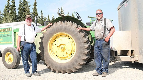 Jeff Newell and Ron Wachholtz stand by Newell's tractor