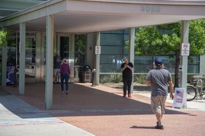 Denton residents walk in and out of the Denton Public Library North Branch this afternoon on voting day. The library served as a polling location for the local precinct.
