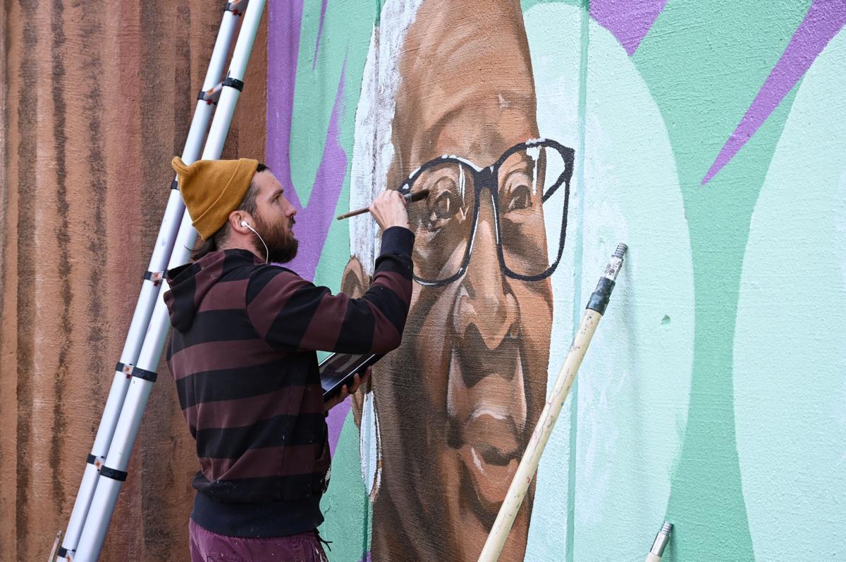 Muralist repaints historical piece at neighborhood gateway