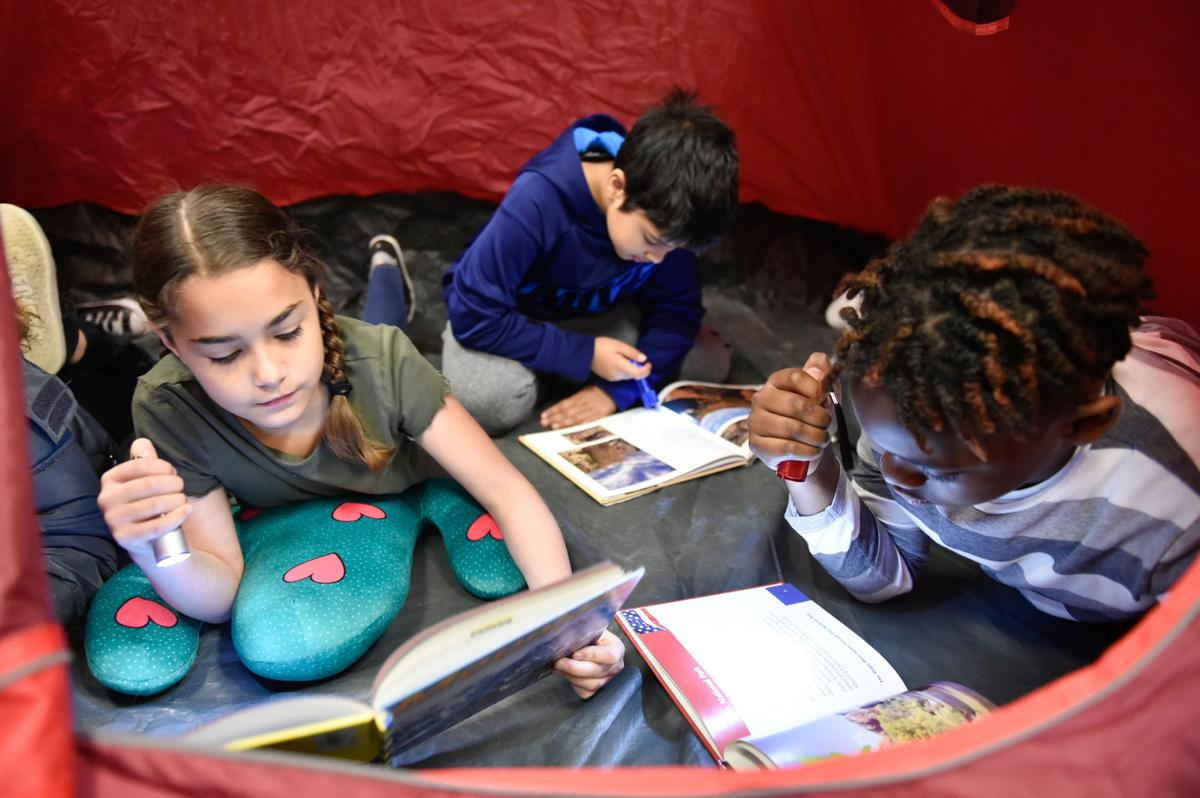 Third-graders reading in tent