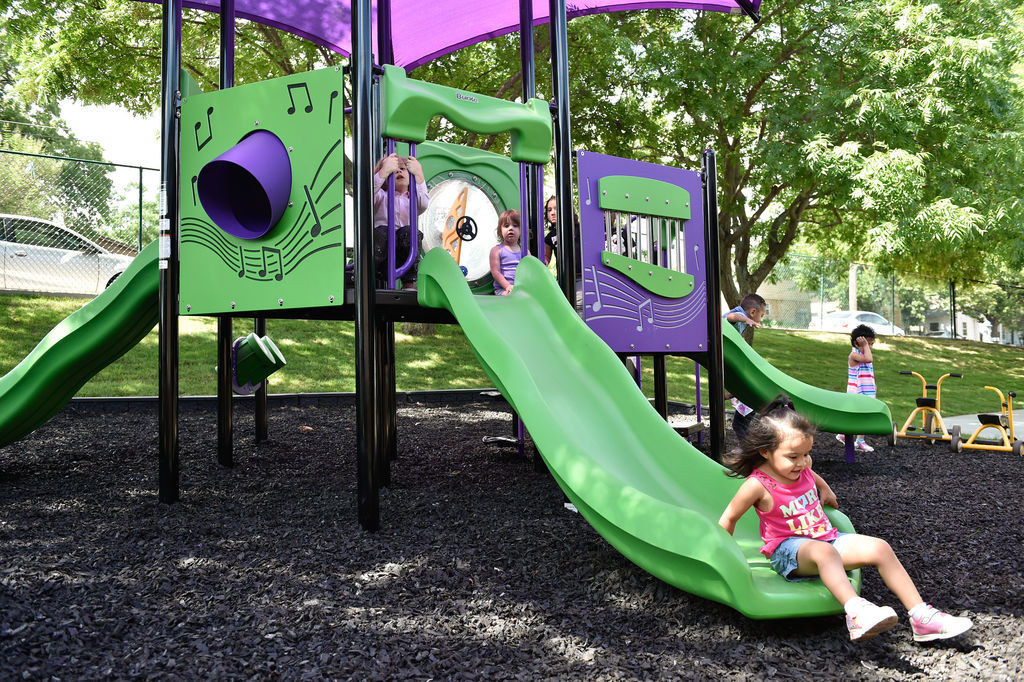 Children have fun on a newly built play area at Fred Moore Day Nursery School.  Floyd Smith Concrete is the company that built the play area at Fred Moore Day Nursery School.  The company is building it through a grant.