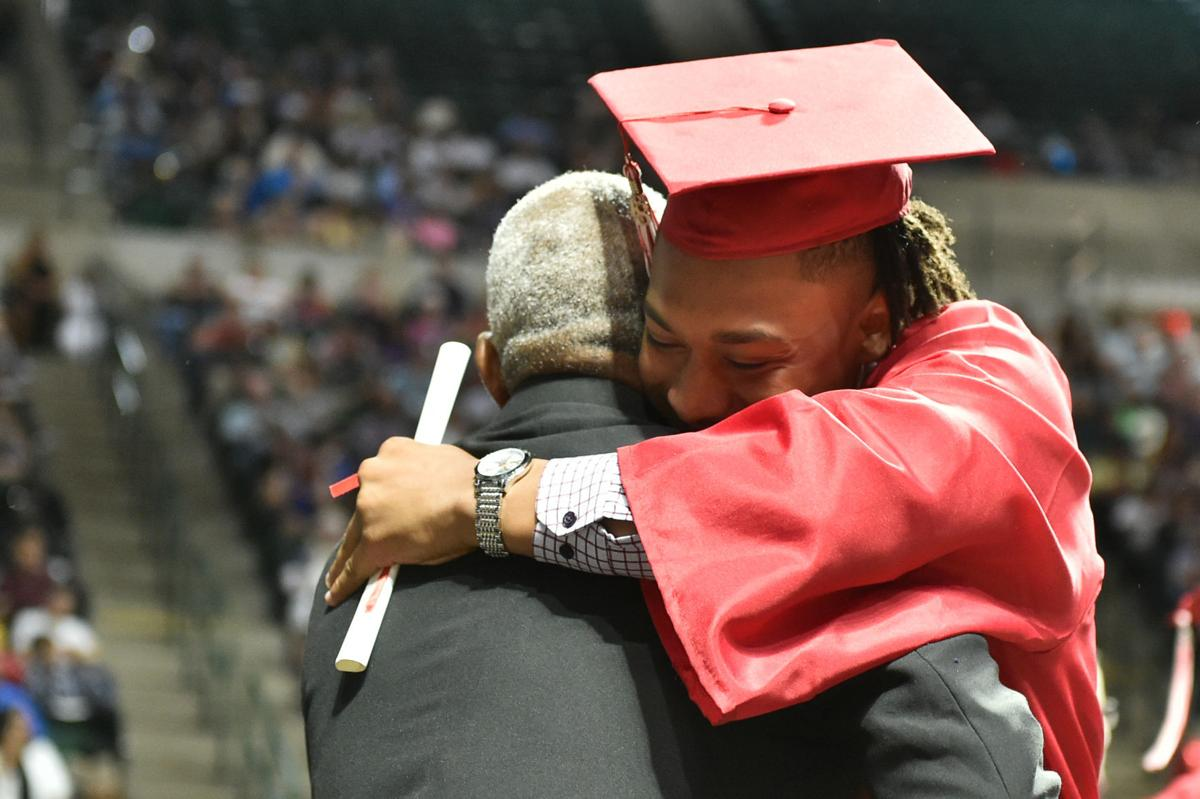 Graduating senior Kosi Eldridge, receives his diploma as he walks the stage during the Ryan High School graduation ceremony at the UNT Coliseum.