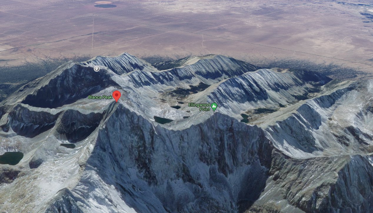 Blanca Peak and Ellingwood Point are labeled in this image. Little Bear Peak is marked by a grey pin behind Blanca Peak. The route most climbers use to access these mountains comes up from the valley (with lakes and green) that can be seen behind the saddle between Blanca Peak and Ellingwood Point. Image Credit: @2021 Google Maps.