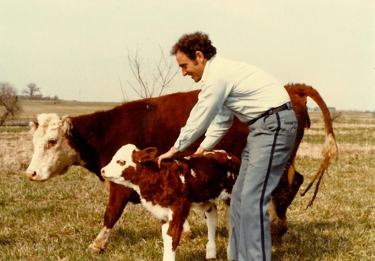 Dale Kilburg as a young man with a cow and calf