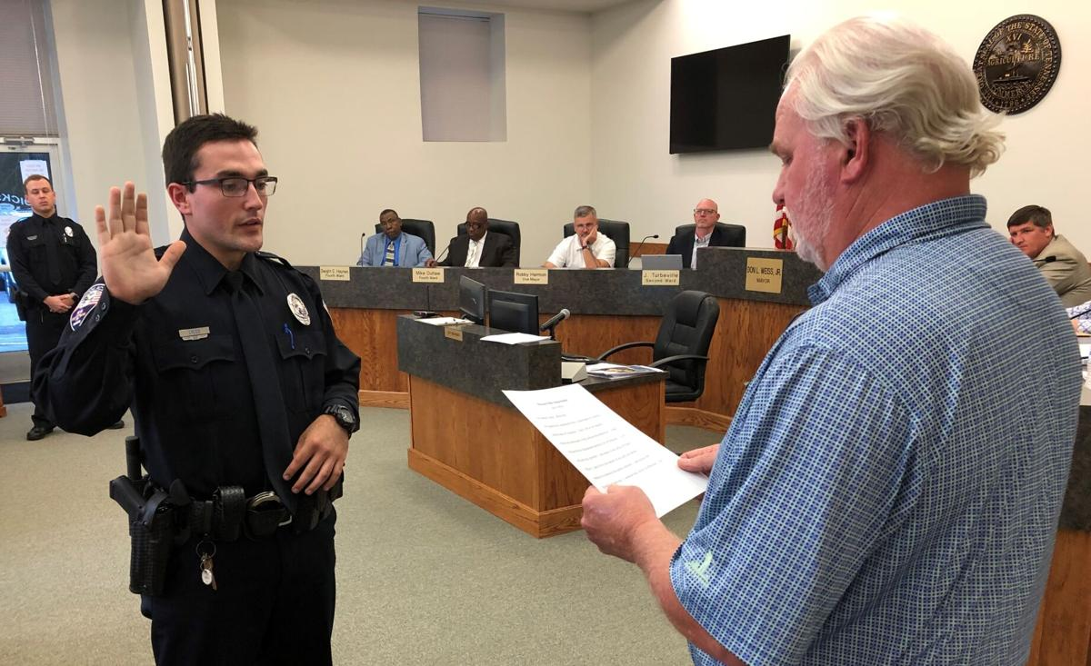 New Dickson Police Department Officer Kendell Lyles (left) receives the Peace Officer's oath from Dickson Mayor Don L. Weiss Jr.