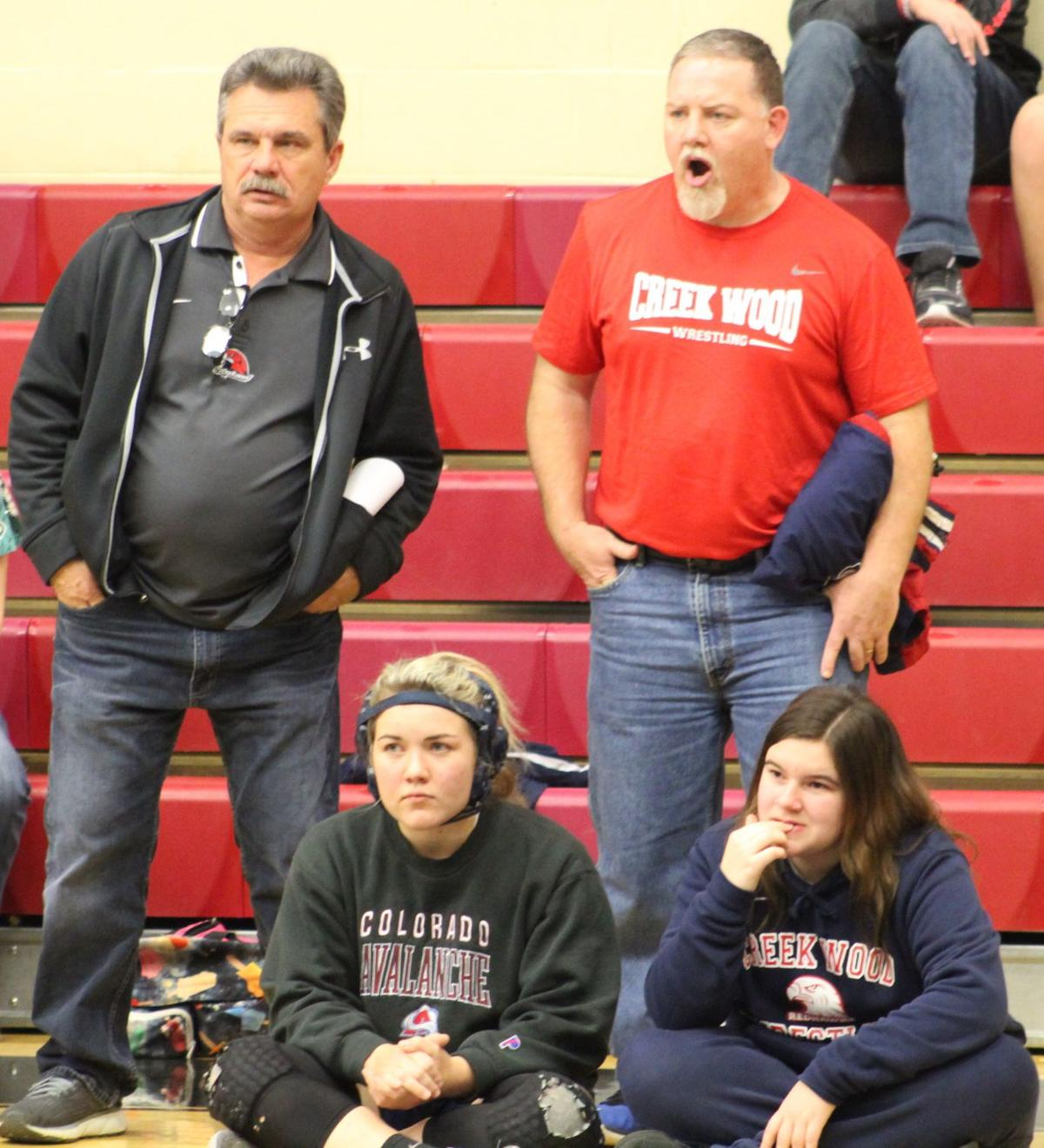 The Creek Wood wrestling coaches and few members of the team look on during a match.JPG