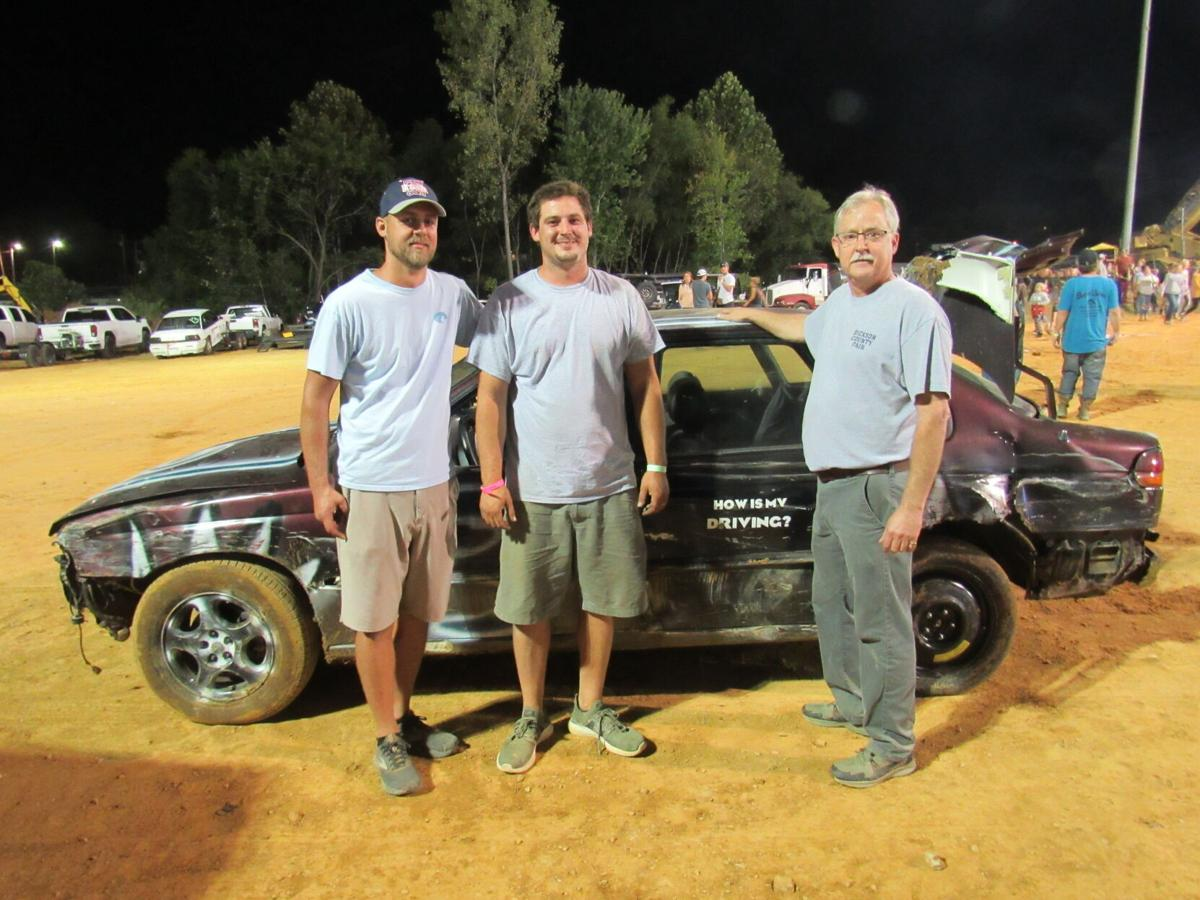 (left to right) Jump-n-Run director Aaron Lampley, Jump-n-Run contestant Nathan Manley, and fair board member Horace Perkins in front of Manley's car after Manley's second night of competition. SHARON ALICE LURIE