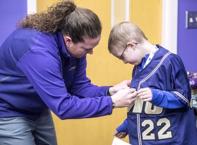 d18593792a2 JMU softball assistant coach Jennifer Herzig buttons up a jersey for  8-year-old McKenzie Woods