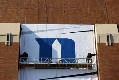 Workers hang the Duke Blue Devils logo on the side of Lucas Oil Stadium home of the 2015 Final Four on April 1, 2015 in Indianapolis, Indiana.