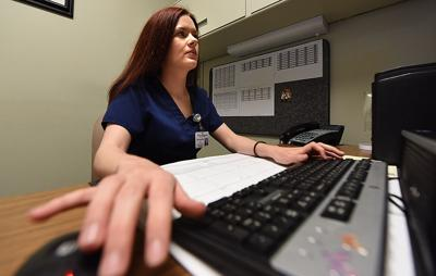 JAY HARE / DOTHAN EAGLE Patient Services Supervisor Samantha Evans looks over a patient record at Flowers Hospital on Friday.