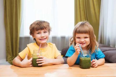 Two Cute smiling kids drinks healthy green smoothie with straw in a jar mug at a table in the home.