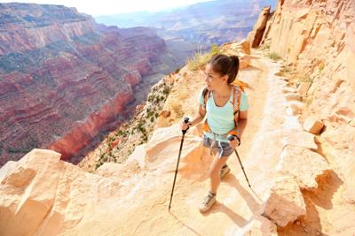Hiker woman hiking in Grand Canyon walking with hiking poles. Healthy active lifestyle image of hiki