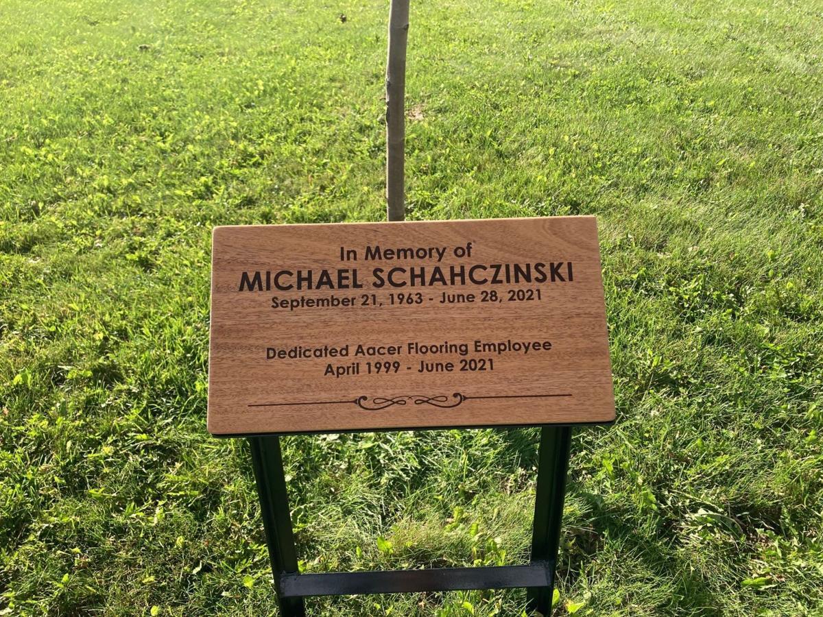 Plaque stands in front of maple tree in memory of Michael Schahczinski