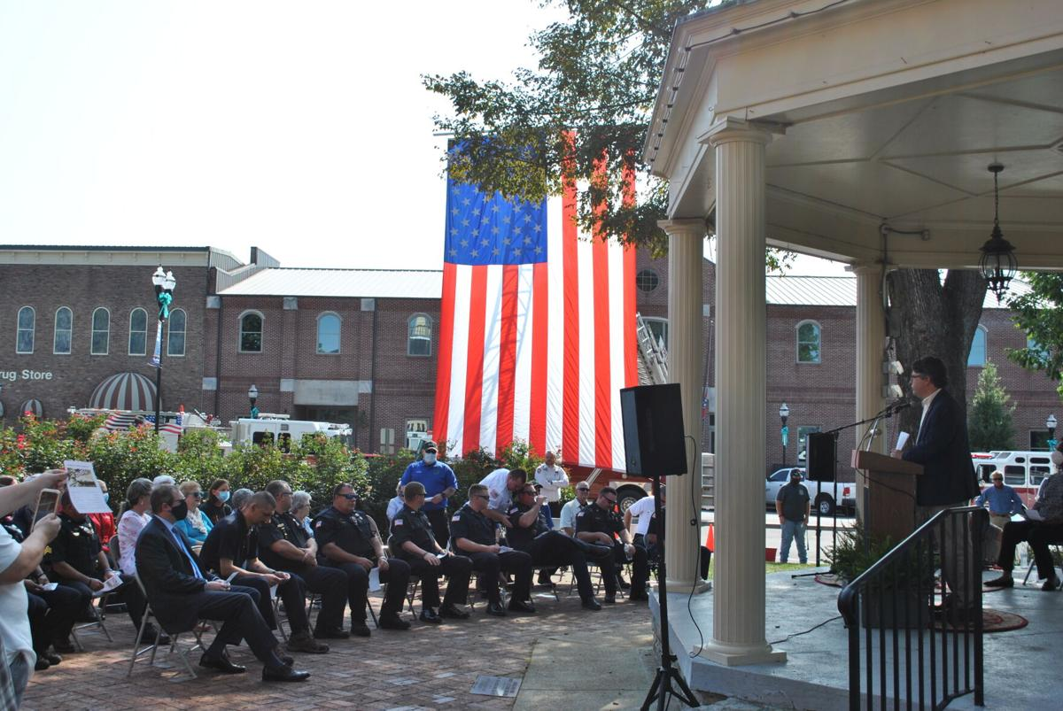 Fayetteville first responders look on in the shadow of the American flag as speeches are given in remembrance of the lives lost and heroism displayed on September 11, 2001.