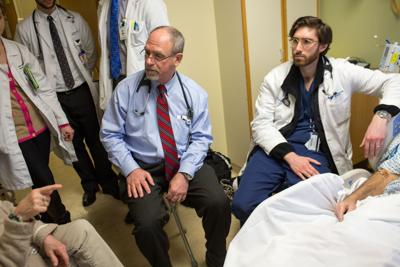 Dr. Michael Bennick, left, medical director for patient experiences at Yale New Haven Hospital, during a visit to a patient with medical students and residents.
