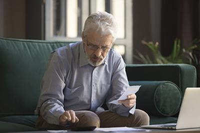 Mature man holding receipt calculates on calculator monthly expenses