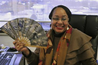Sharon Brown fans herself to help her with hot flashes at her desk in Winston-Salem, N.C.