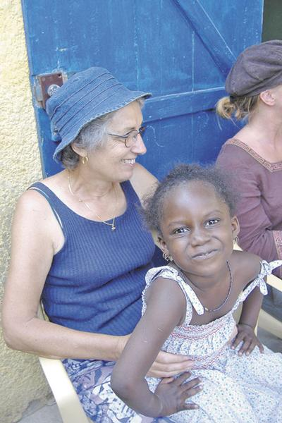 A senior volunteer working with a child in Senegal in a Projects Abroad program.