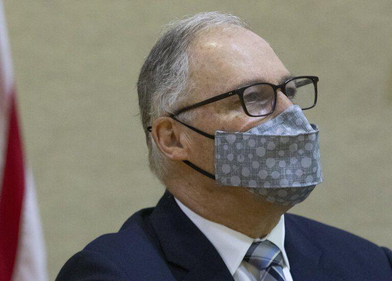 Gov. Jay Inslee in a dark blue suit and light gray mask with polka dots looks off to the right, with a beige wall behind him and the corner of an American flag on the left side of the frame.