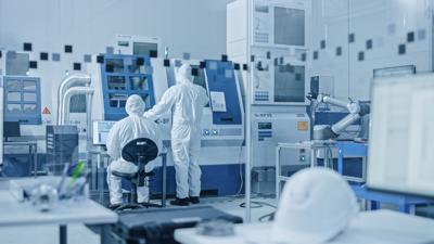 Sterile Modern Factory: Professionals in Coveralls, Masks Working on CNC Machinery. Medical Electronics Manufacturing Laboratory with High Tech Robot Arm Production Line and Contemporary Equipment