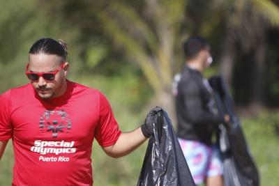 Un grupo de voluntarios de Special Olympics limpia una playa en Piñones