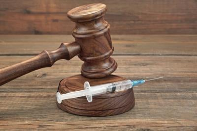 Judges Gavel And Syringe On Brown Wooden Background Close-up