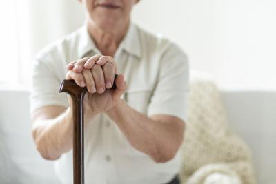 Close-up of hands of an elderly man holding onto a cane