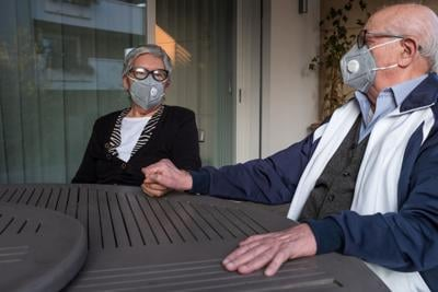 An elderly couple wearing a protective mask and holding hands. They are sitting at terrace of their house in Brescia, Lombardy, Italy.