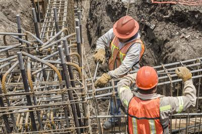 Construction workers laying the foundation with iron rods