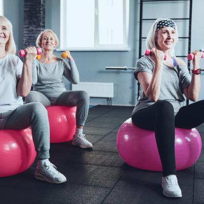 Senior women exercising with dumbbells on fitness ball in gym