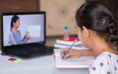 Concept of homeschooling or e-learning, young girl busy in writing by looking into laptop while teacher explaining during covid-19 or coronavirus pandemic crisis.