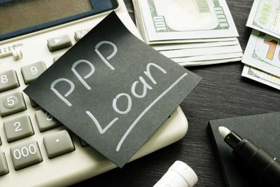 Memo sign PPP Loan Paycheck Protection Program on the black piece of paper.
