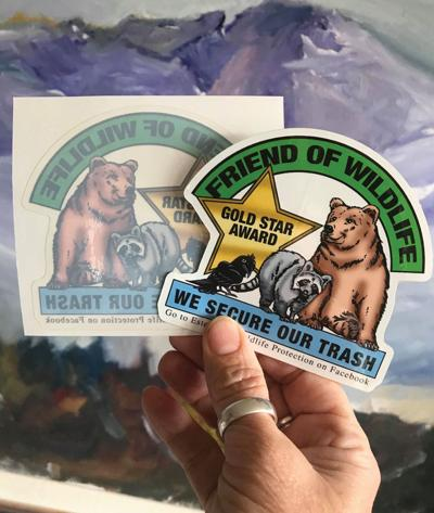 """By: Kris Hazelton There is a group of friends in Estes Park who love our wildlife and don't want to see any of them killed due to the negligence of residents and businesses who do not secure their trash. They have come up with a novel idea to help save our bears. The group designed this colorful sticker which they hope businesses will want to display on their front window, on their dumpster, at their front desk, etc. The sticker is a Gold Star Award for being a Friend of Wildlife. The group says, """"Being responsible with our trash 100%of the time can really go a long way to help save our bears. This sticker was created to remind everyone to be more responsible while living or recreating here, in bear country."""" They added, """"We want to remind residents and visitors to practice proper food storage and trash disposal at all times. Intentional or unintentional feeding of bears can result in the bear being killed and/or fines for not complying with our Wildlife Protection Ordinance. Every year, law enforcement and Colorado wildlife officers respond to hundreds of calls in which bears may pose a public safety threat and/or are damaging property. In some cases, the animals are euthanized. We can all become part of the solution and help us save our Estes Park bears by earning a Gold Star Award."""" In order to obtain this sticker, businesses must agree to always secure their trash in a bear proof dumpster or trash recepticle. They also must instruct and work with their employees and/or co-workers to do the same. Leaving a dumpster or trash recepticle open, even once, is the same as leaving the front door wide open and is a sure way to kill our wildlife.  Black bears have a highly specialized sense of smell, which lead them to where they may quickly find an overflowing garbage can or someone's leftover hamburger and French fries. We can help bears stay out of human territory and stick to their natural diet by properly disposing of leftover food and garbage. Garbage is irresistibl"""