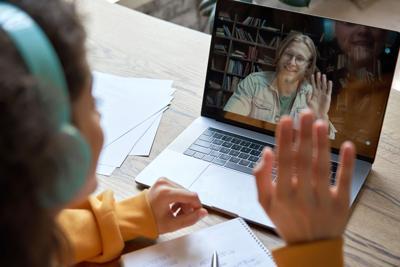 Hispanic teen girl distance learning with online teacher on laptop screen.