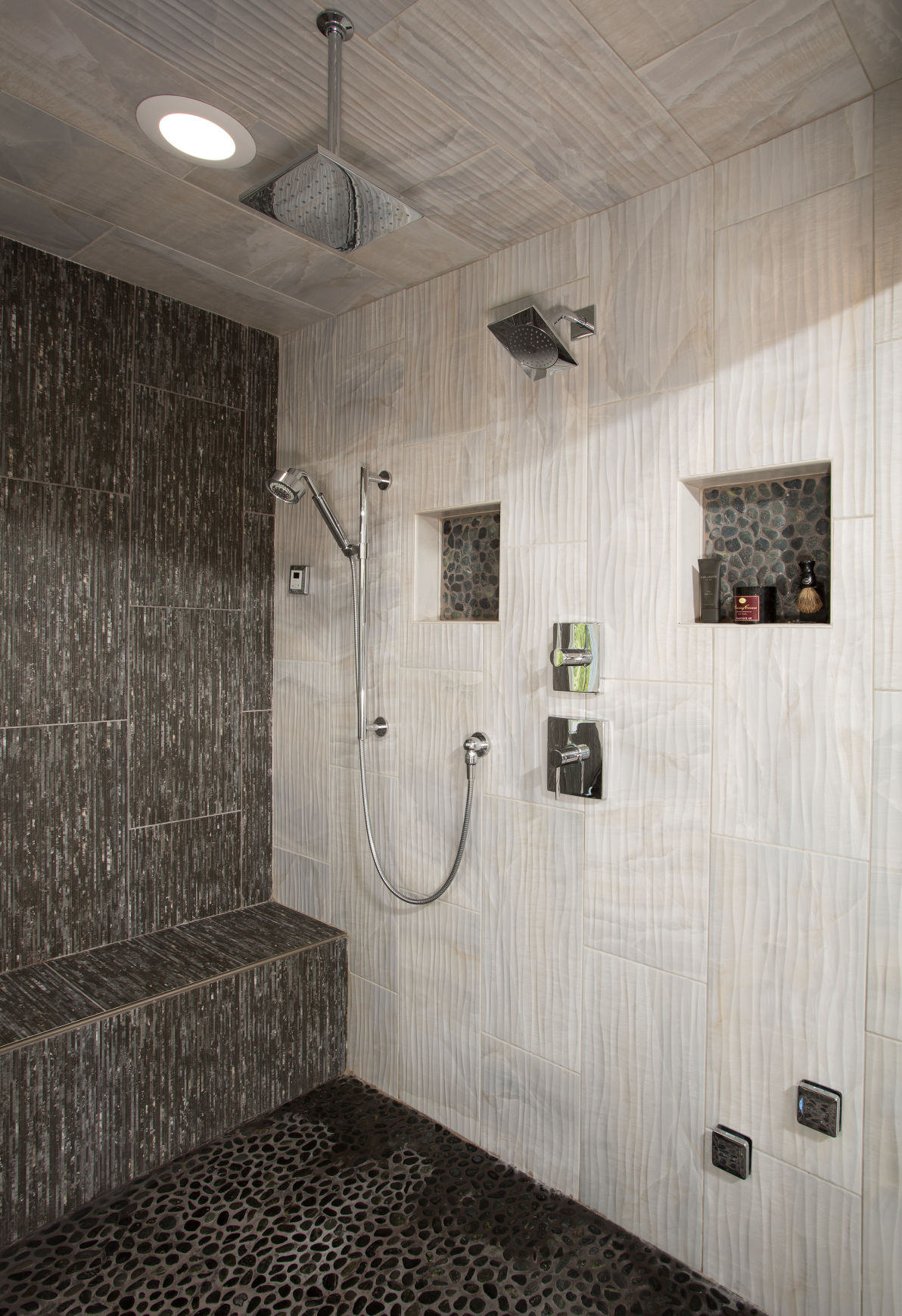 The Showeru0027s Inside Wall Is Finished In Contrasting Light And Stone Tiles  With A Softly Accentuated Moire Pattern; There Are Three Shower Heads And A  Long ...