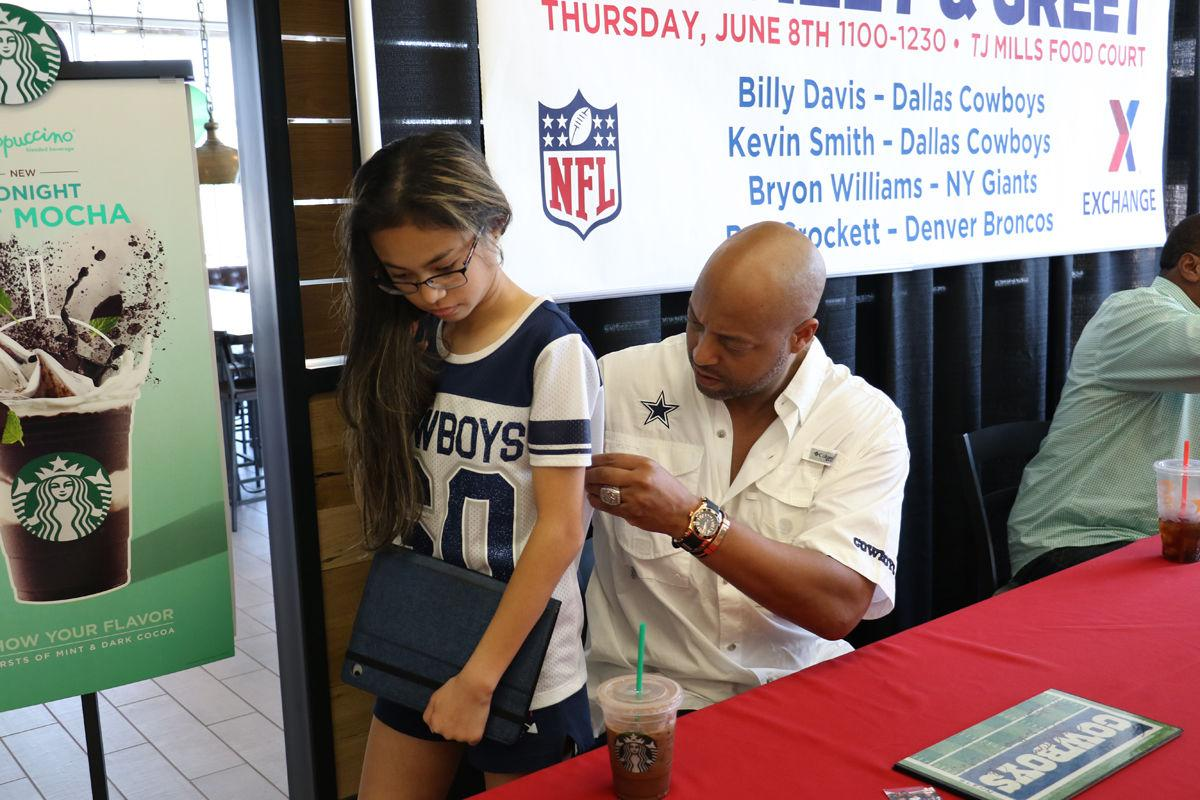 Former nfl players meet fans show support sports former dallas cowboys wide receiver billy davis signs the back of a cowboys jersey for kaella glenn 14 june 8 during a meet and greet at the tj mills food m4hsunfo