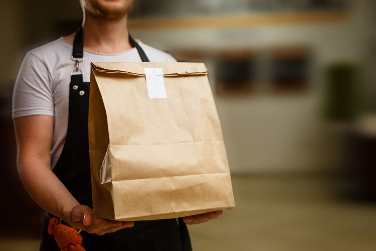 Diverse of paper containers for takeaway food. Delivery man is carrying