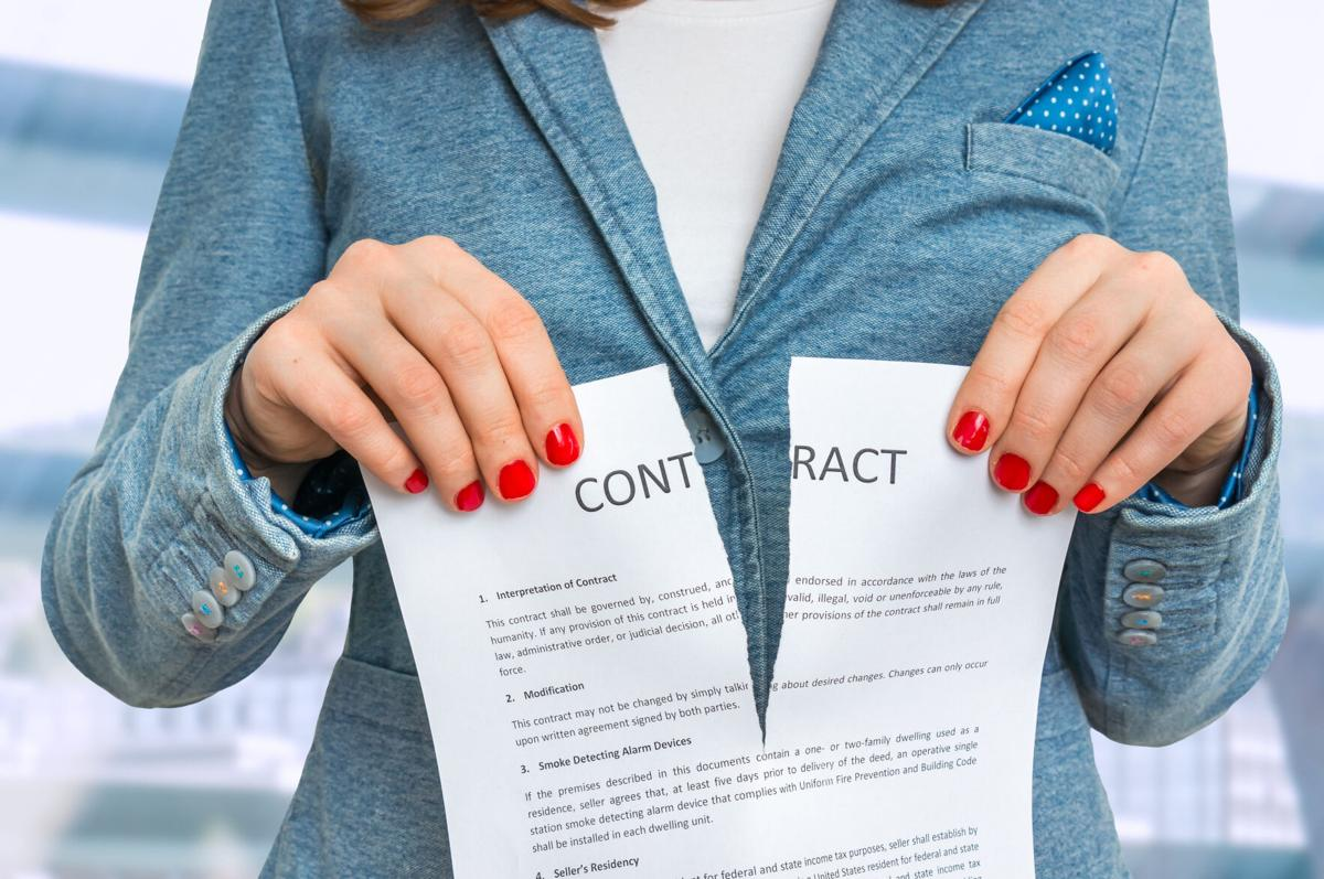 Business woman tearing contract in office