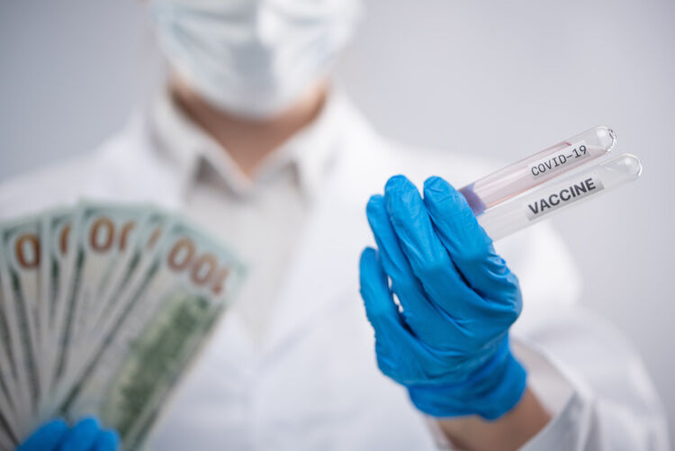 Close-up view of doctor in biohazard protective clothing keeps money and covid-19 vaccine on white background. Scientific discovery reward. Healthcare and coronavirus infection concept.